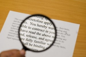 """Magnifying glass on a contract with selective focus on the word """"contract""""."""